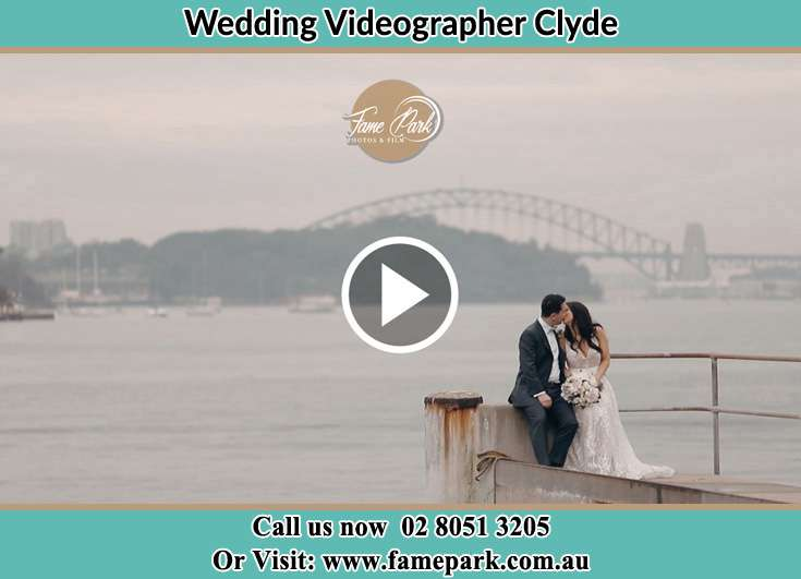 Bride and Groom kissed while sitting near the shore Clyde NSW 2142