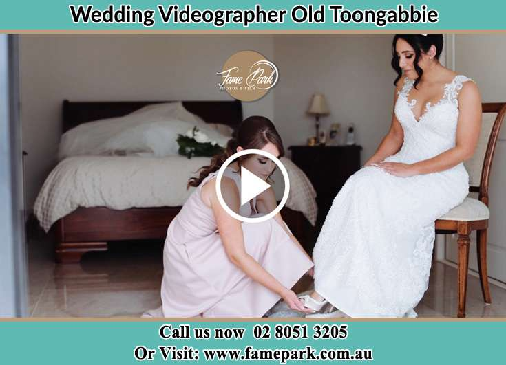 A bridesmaid trying to put the shoes on the Bride's foot Old Toongabbie 2146