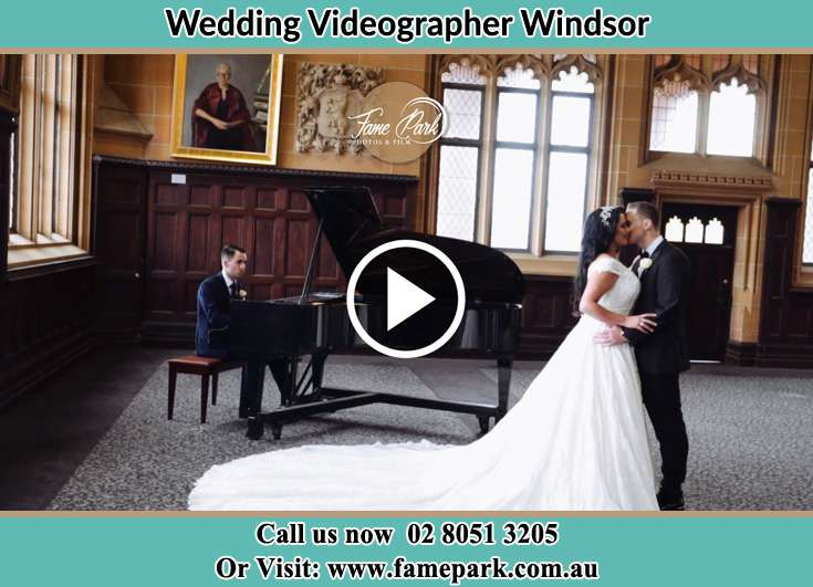 The newlyweds kissing with the pianist playing music Windsor NSW 2756